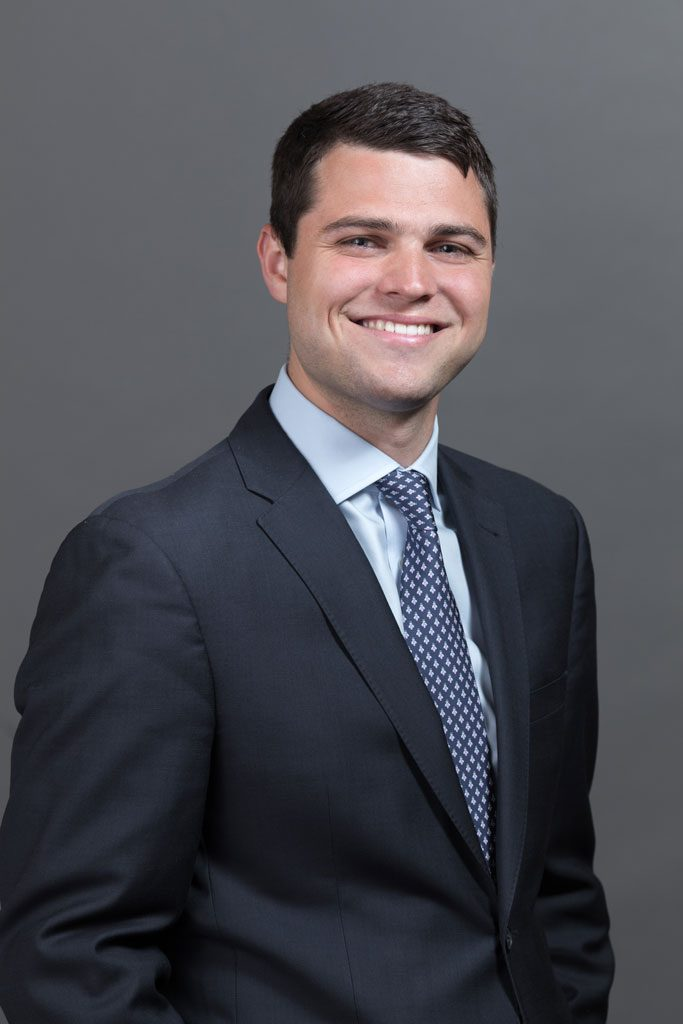 corporate headshot of man in suit
